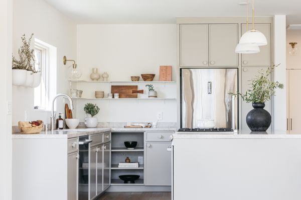 White kitchen with stainless steel appliances and neutral decor items and houseplants