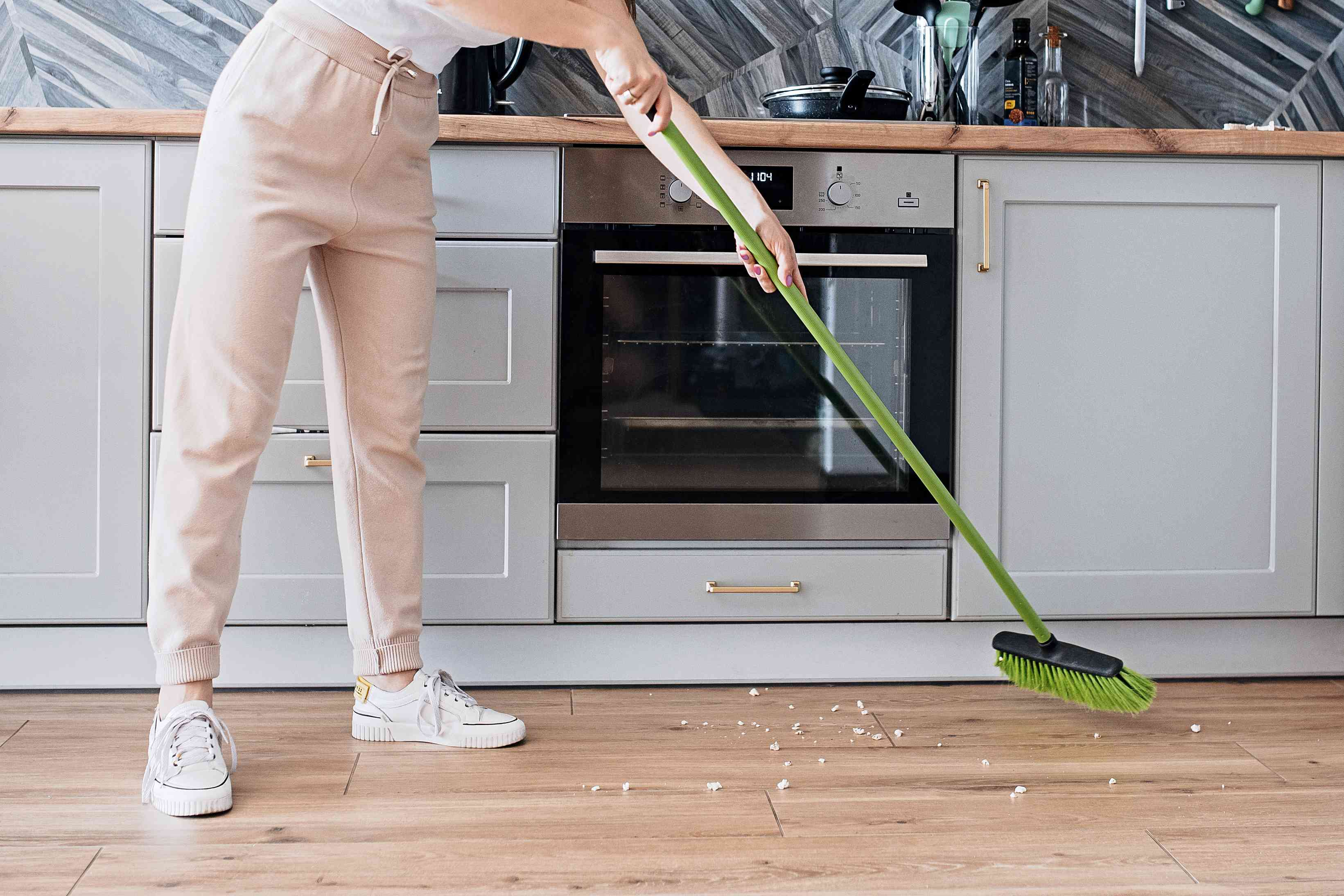 Green broom sweeping white debris in long stroke
