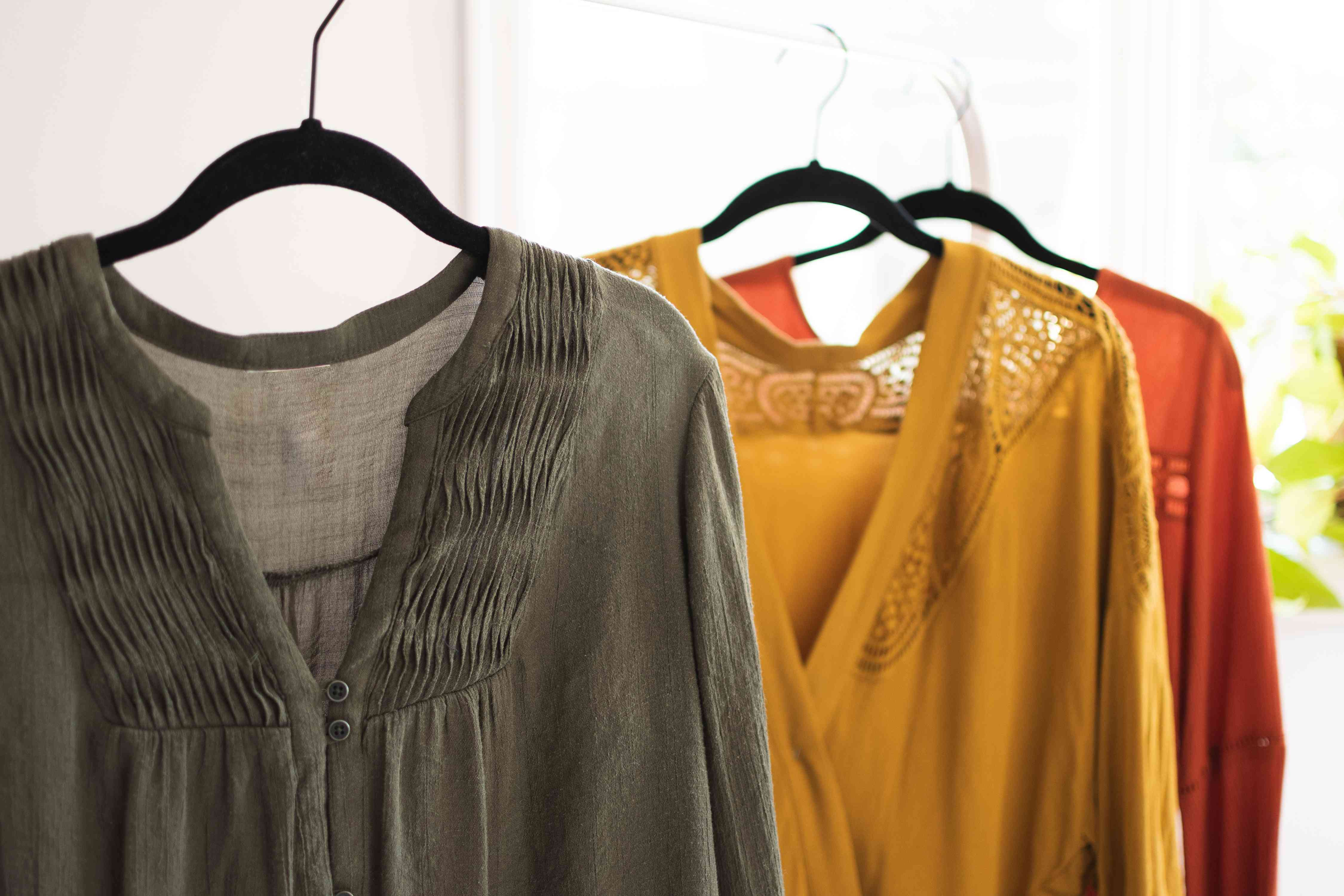 Green, yellow and red rayon blouses hanging on black hangers