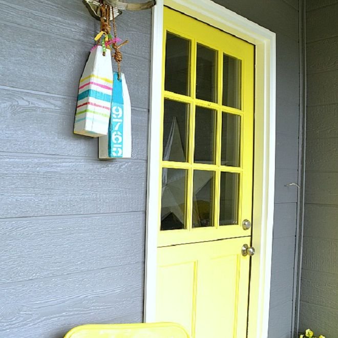 Address number signs on colorful painted buoys next to a yellow door.