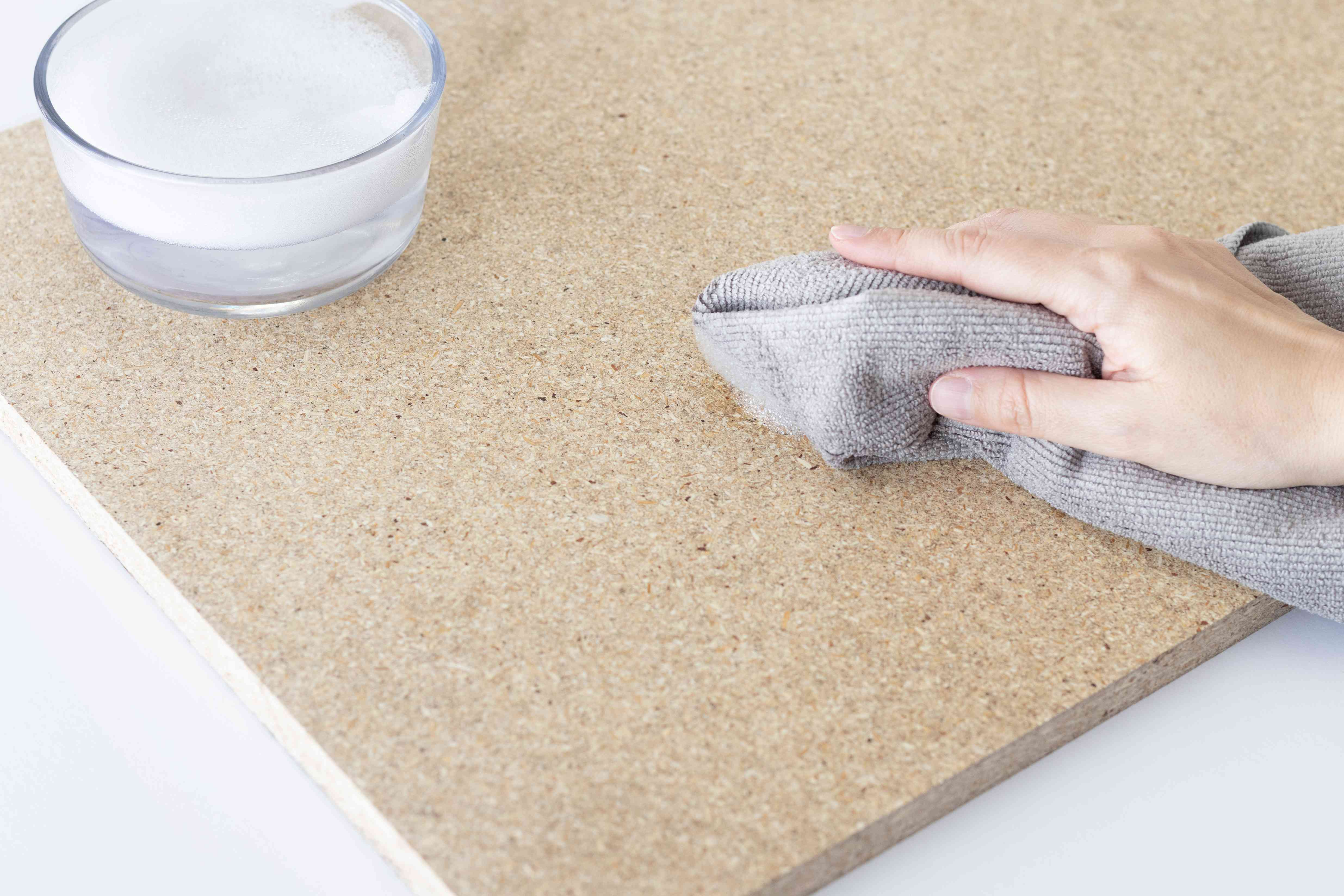 wiping down the shelf surface before applying new shelf liner