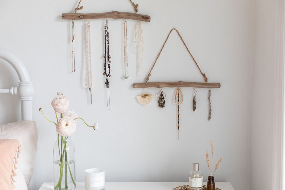 Jewelry hanging from driftwood with hooks over nightstand with decor items closeup