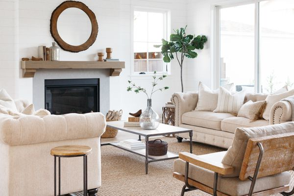 Living room with tan furniture surrounding fireplace and statement plant in corner