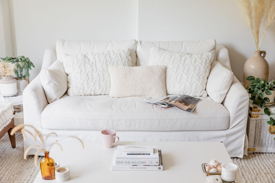 White couch with white throw pillows behind white table with decor items and stacked books