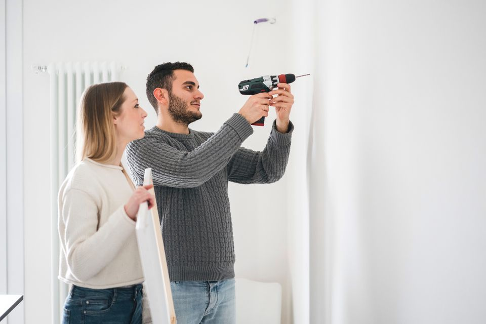 A couple using a power drill