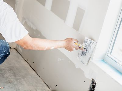 Person using spackle on wall