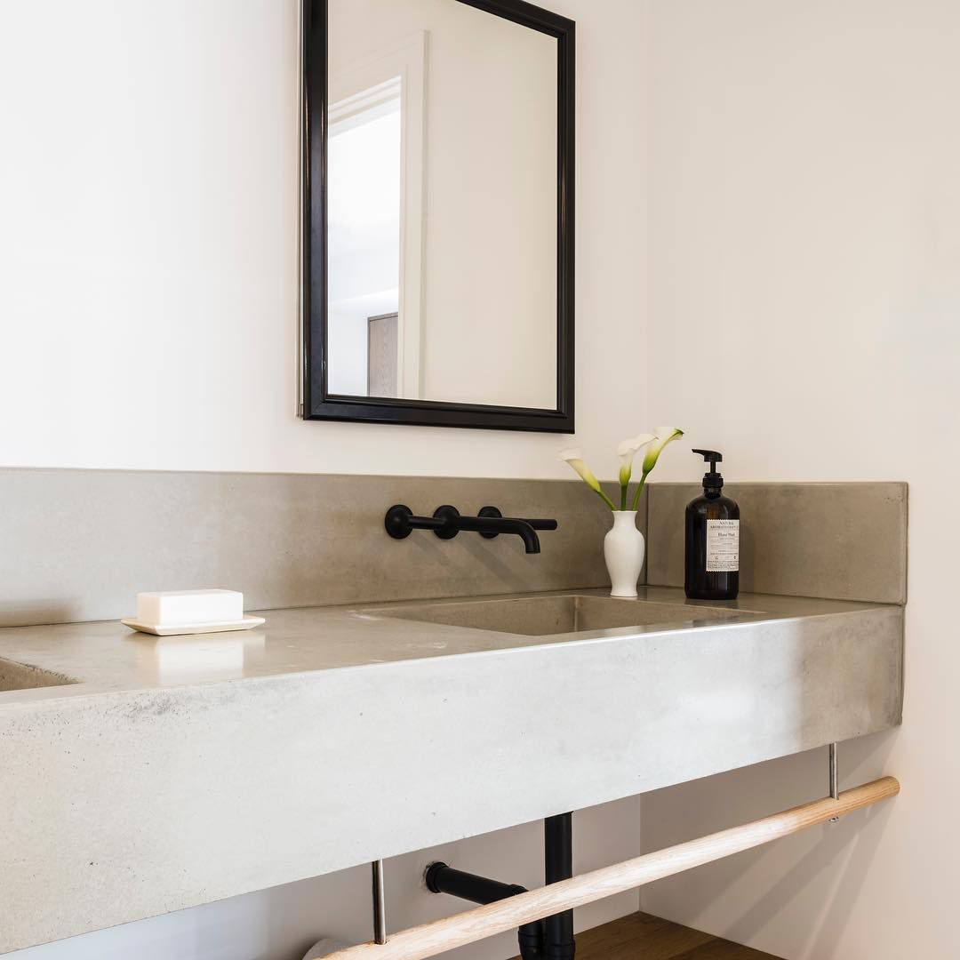 Concrete bathroom sink with mirror and black faucet.