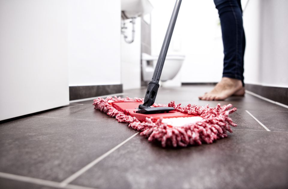 Woman wiping the floor in bathroom