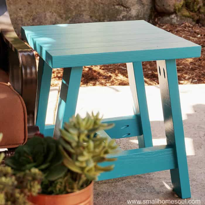 A blue end table sitting on a porch