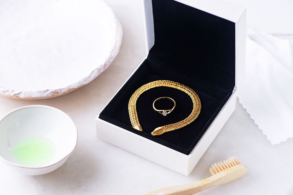 Gold bracelet and ring in black encased box next to tooth brush and dishwashing liquid