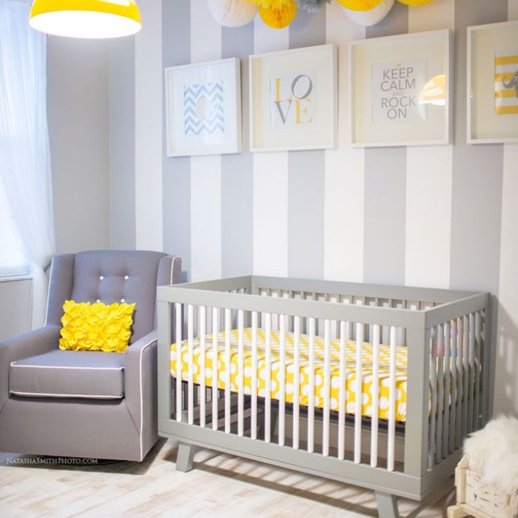 Gray and yellow nursery with striped accent wall and yellow paper pom-pom mobile