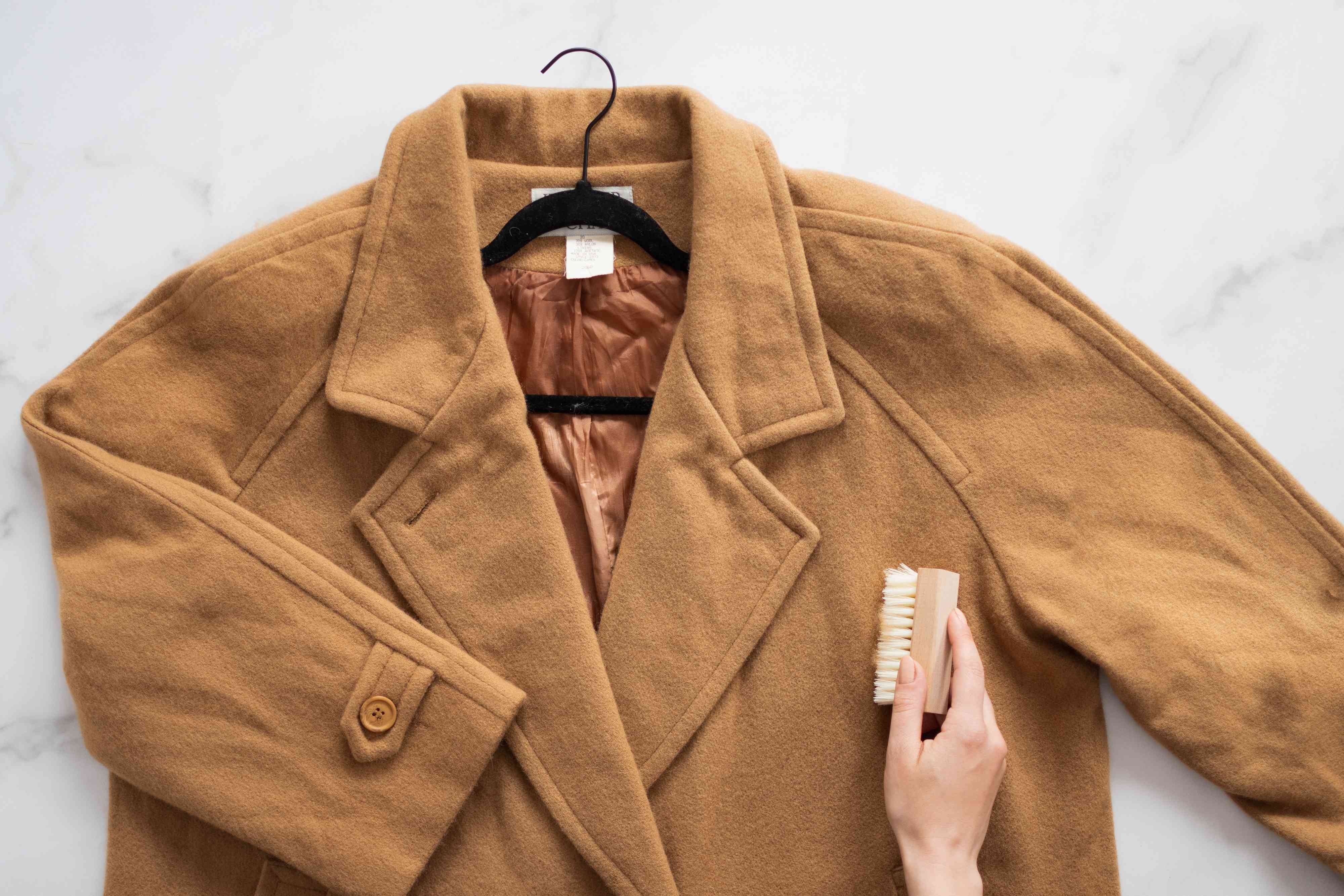 Tan wool coat on black hanger brushed with clothes brush to loosen soil