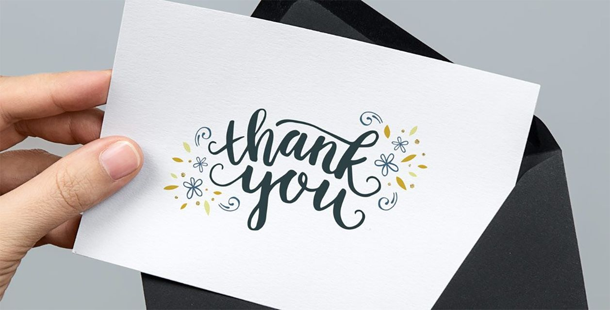 A hand holding a thank you card