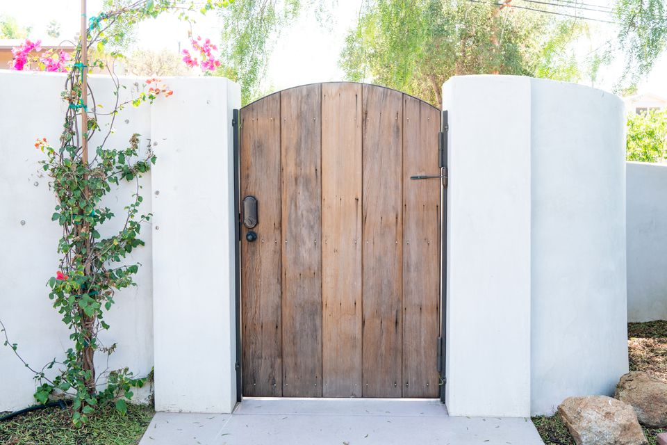 Wooden door in middle part of white stone gate with climbing flowering vines