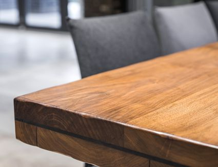 Close-up of corner of acacia wood dining table.