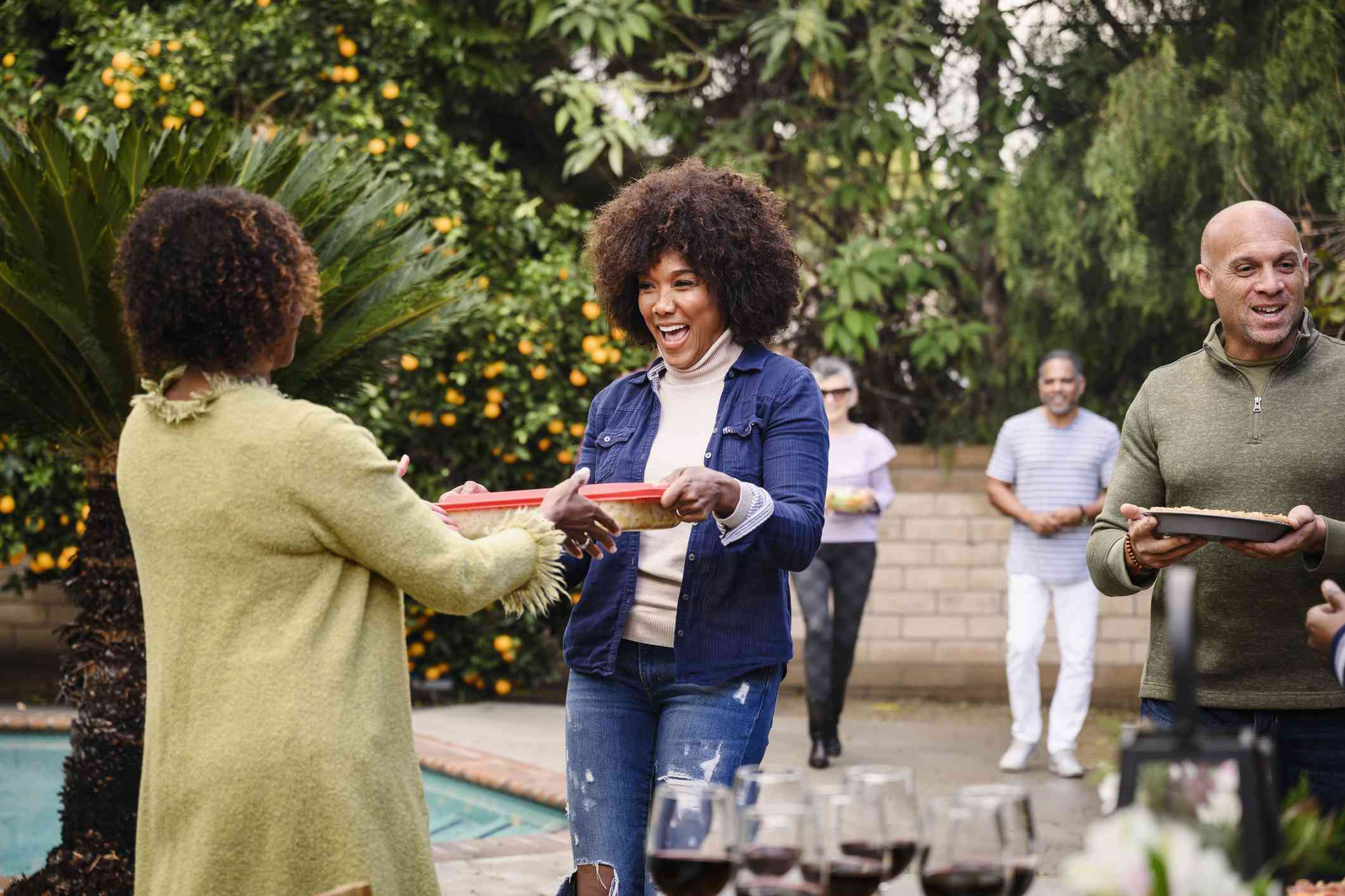 Smiling friends walking into backyard party with trays of food