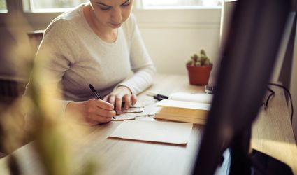 A woman writing in a card at her desk.