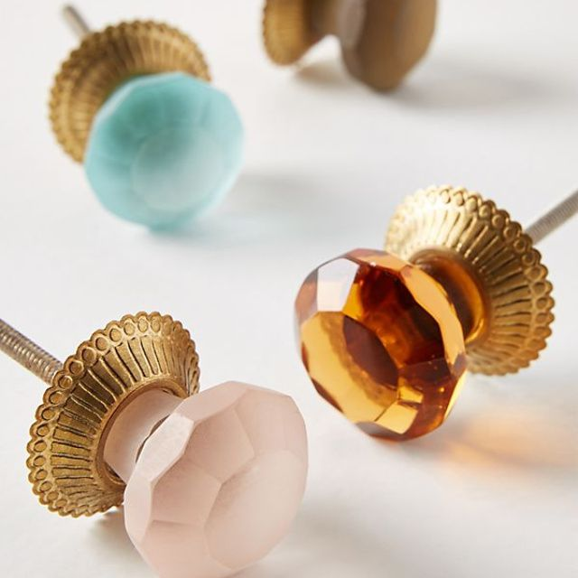 An assortment of gold and pastel colored hardware knobs