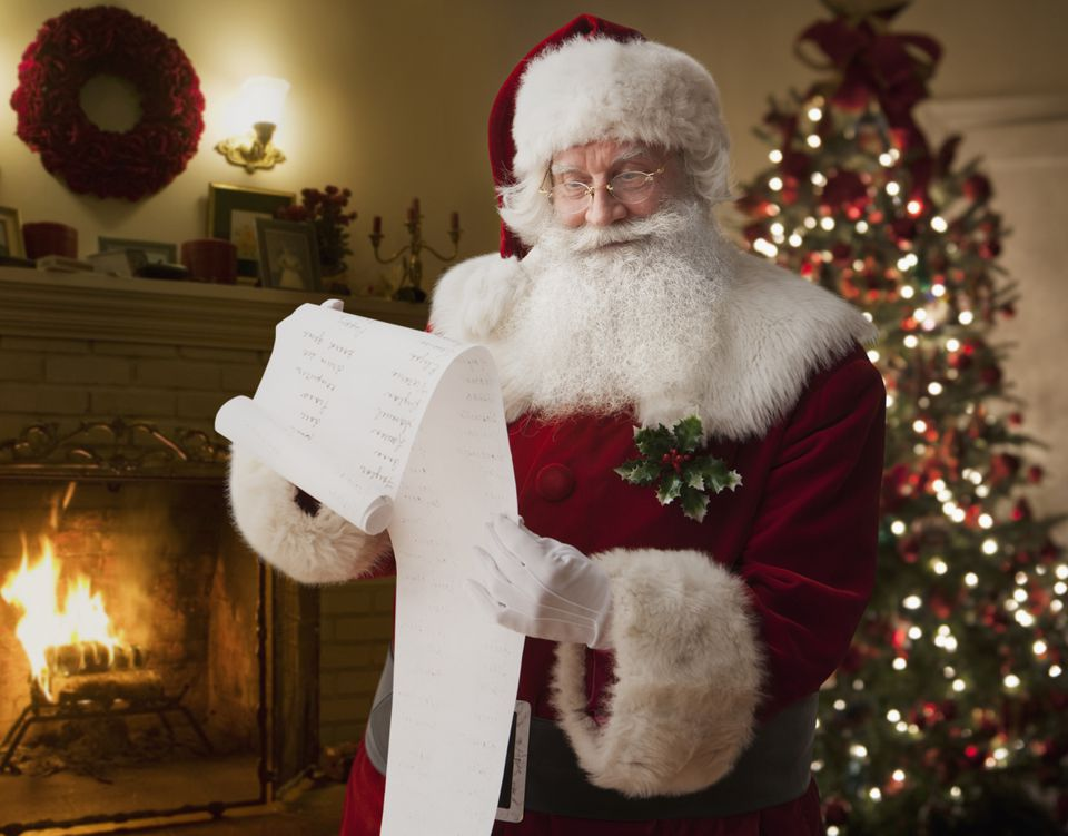 Santa checking his list naughty and nice list infront of a fire