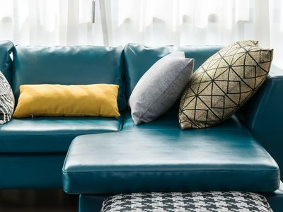 A blue leather couch with throw pillows.