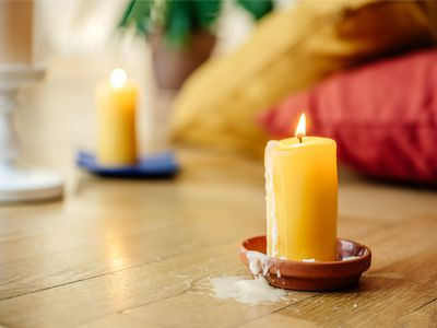 Burning candlestick with dried wax spilled on to wooden floor