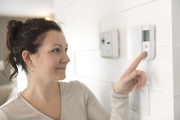 Woman setting a thermostat