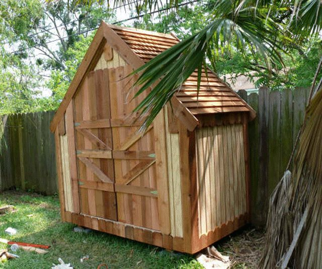 A narrow wooden shed in a backyard
