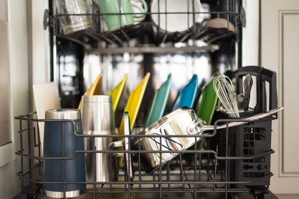 Dishwasher racks filled with pots, cups, plates and utensils