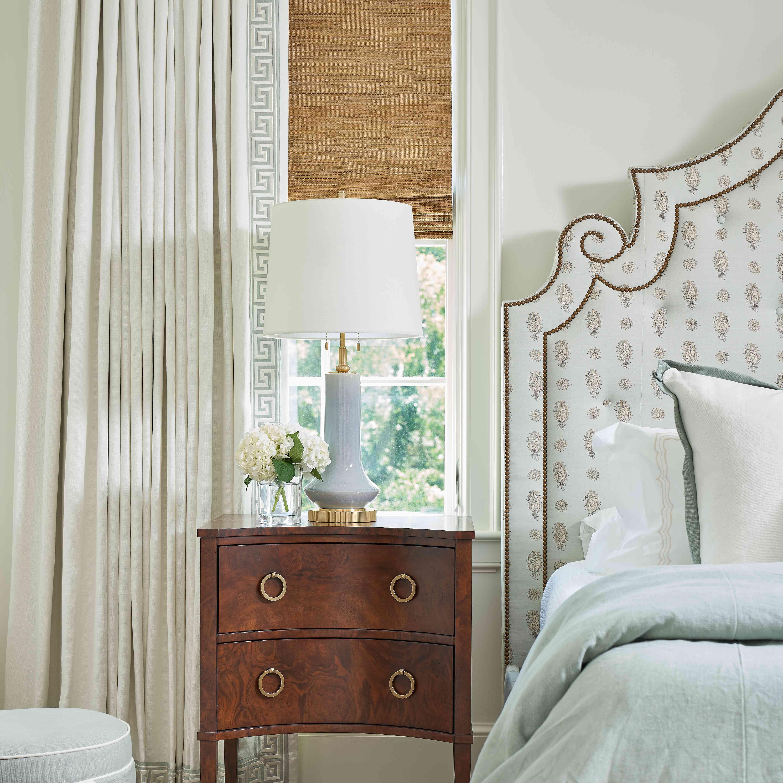 Bedroom with upholstered headboard, wood nightstand, and window