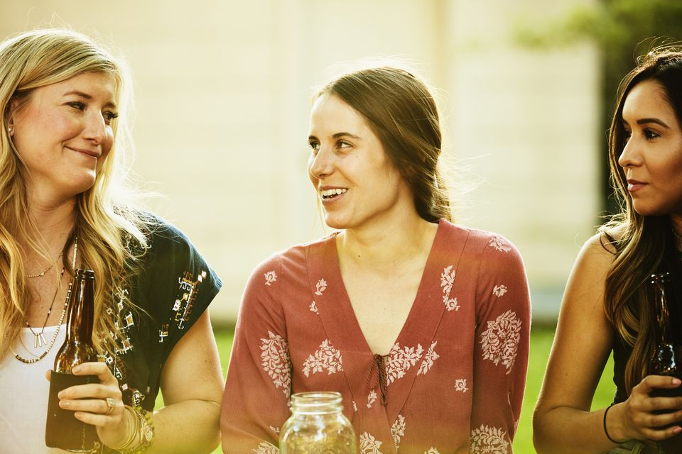 Smiling women sharing drinks in backyard on summer evening