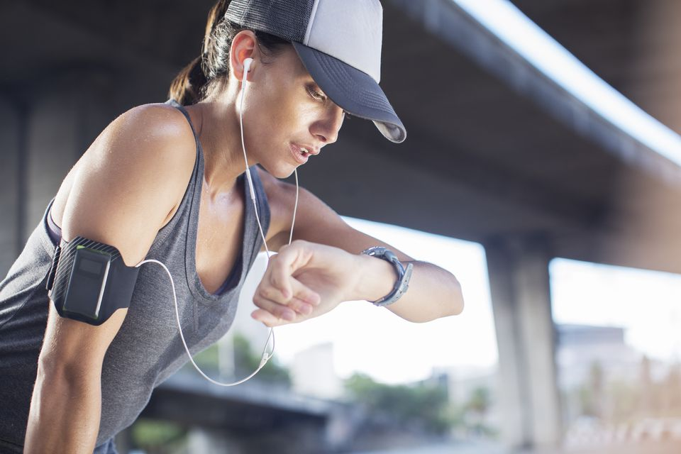 Woman exercising while wearing a baseball hat and checking her fitness tracker on her arm.