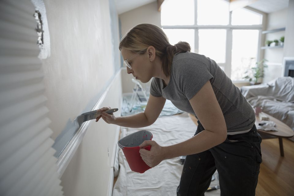 Woman cutting in paint while painting a wall