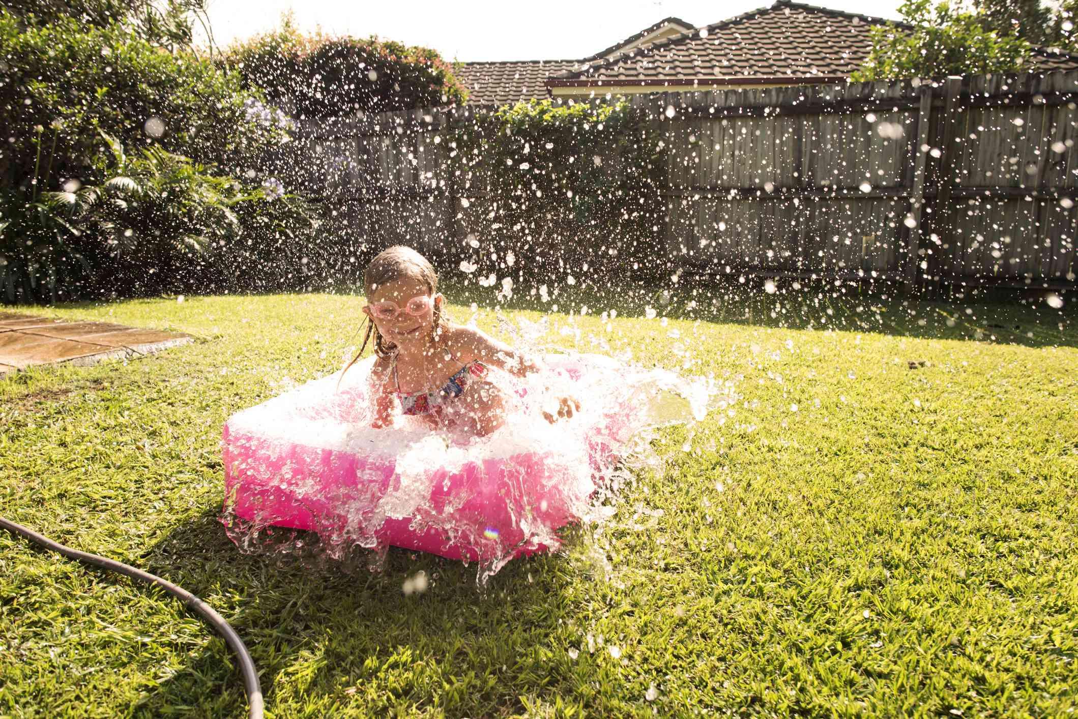 Girl in Australian backyard baby pool splashing