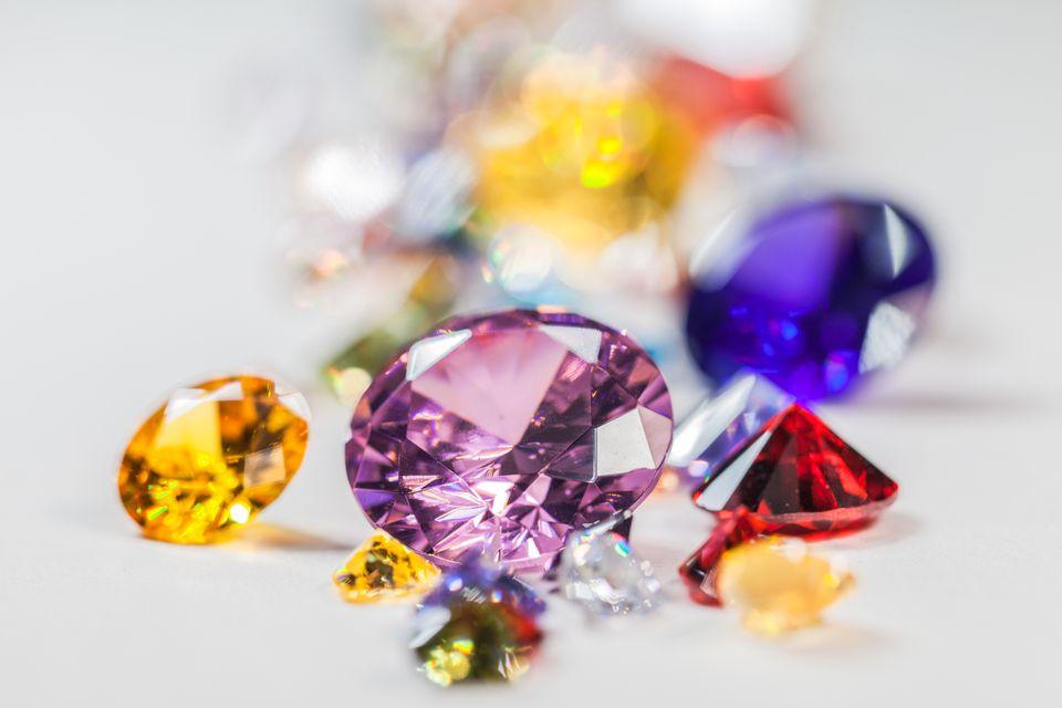 Close-Up Of Multi Colored Pencils Precious Gemstones Over White Background