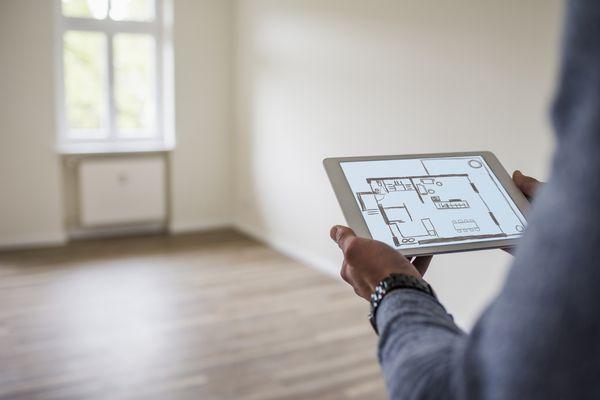 Person reviewing digital floor plan in an empty room