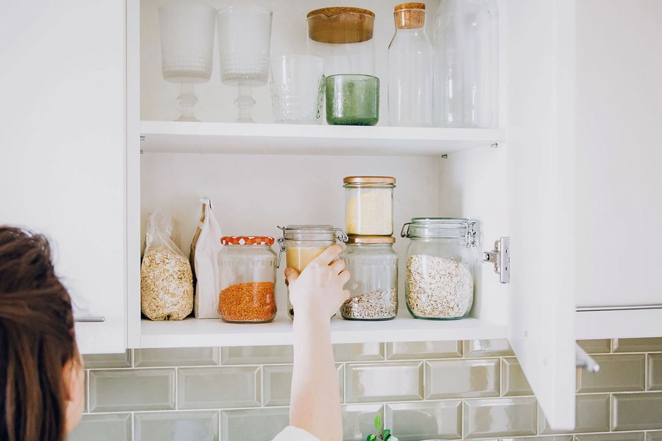 woman putting jars into cabinets