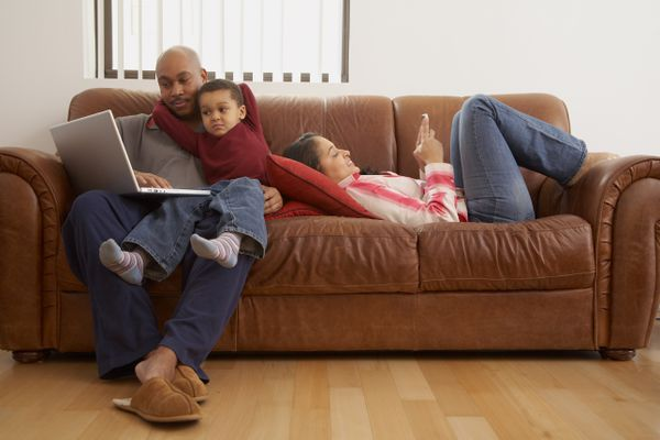 Antiguan man using laptop in living room with family