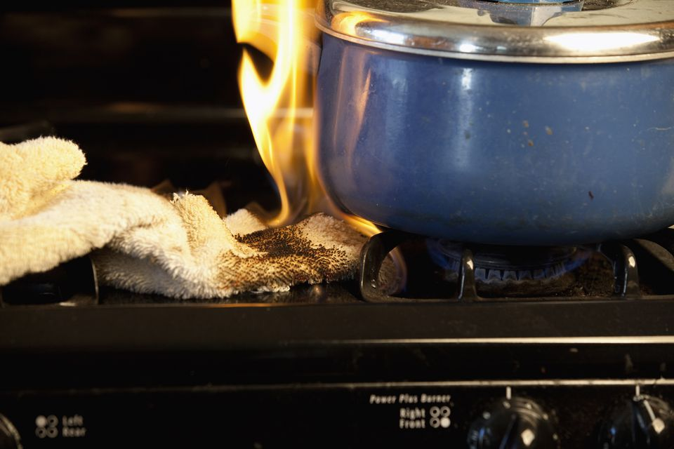 Cloth on fire on stovetop next to blue pot
