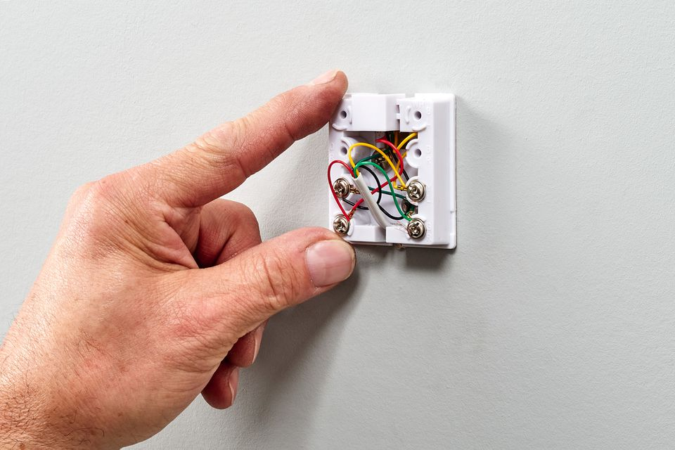 Telephone jack's exposed wires held by hand
