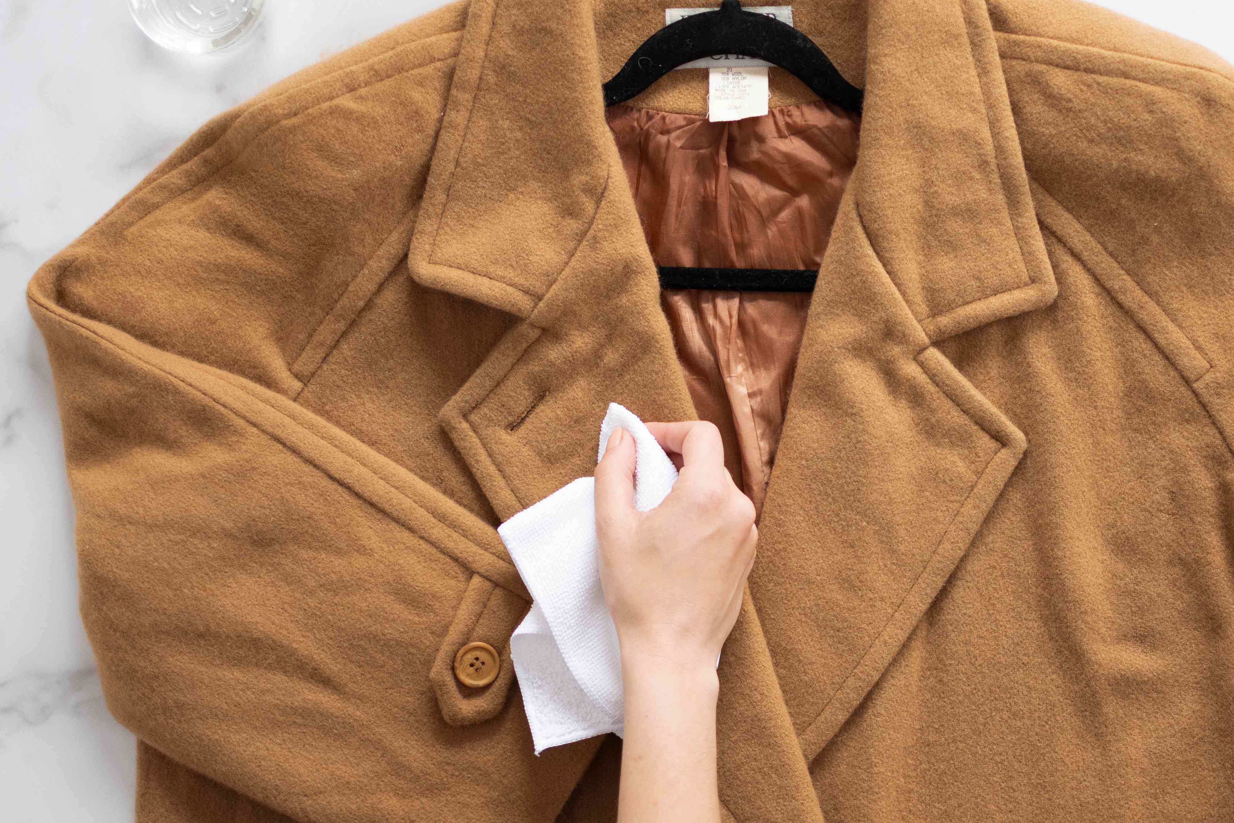 Stain on tan wool coat pretreated with white cloth and gentle wool wash