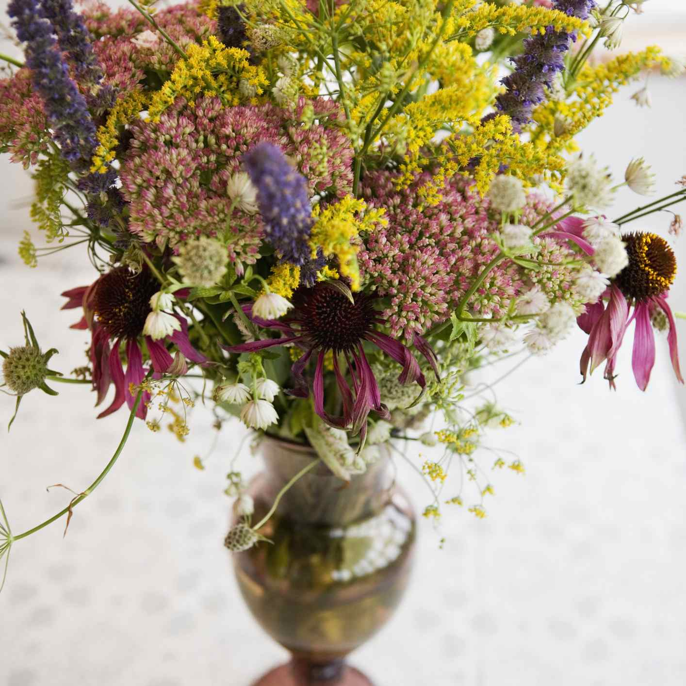 Goldenrod, sedum, and coneflowers in a vase