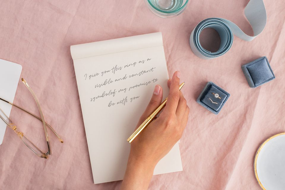 Notepad with wedding vows on pink linen surface next to wedding rings in box