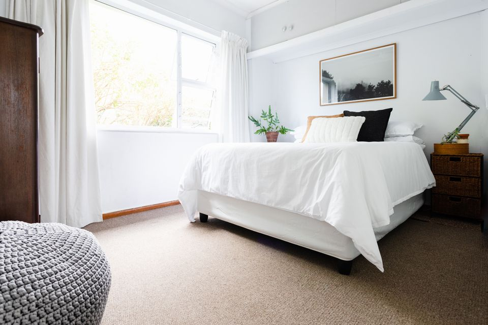 Bed with white sheets and neutral-colored pillows next to brightly-lit window on tan carpeted floor