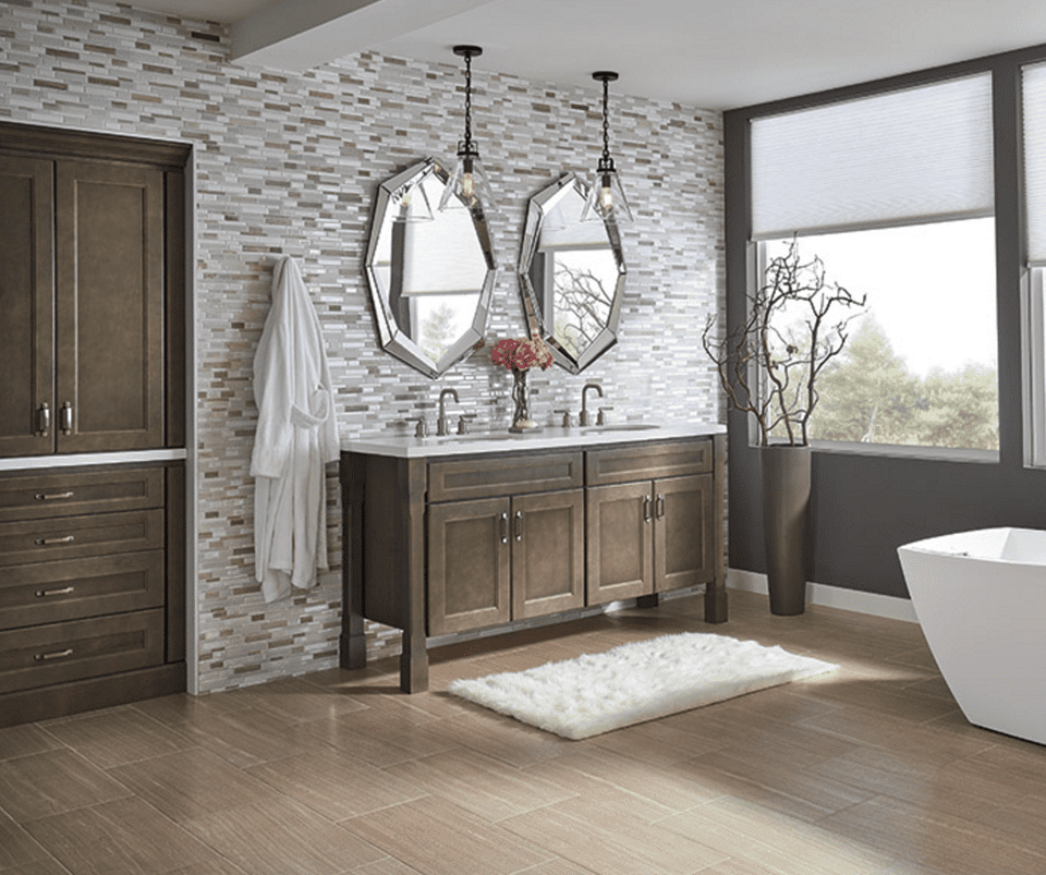 A luxurious bathroom with two mirrors, wooden cabinets, wood floor, and white tub.