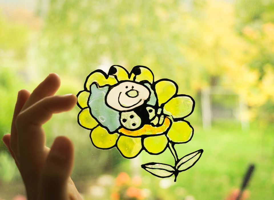 Childs hand with bee and flower sticker on window pane