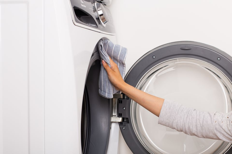 Front loading washer with door open wiped down by hand with gray towel