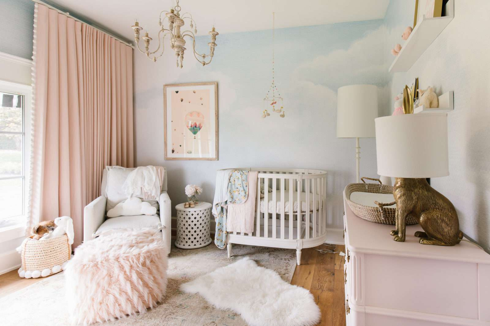 Pink and blue girl nursery with sky mural