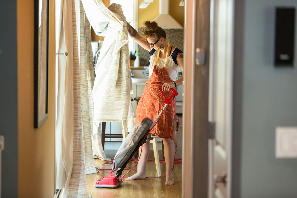 Woman with vacuum cleaning curtains