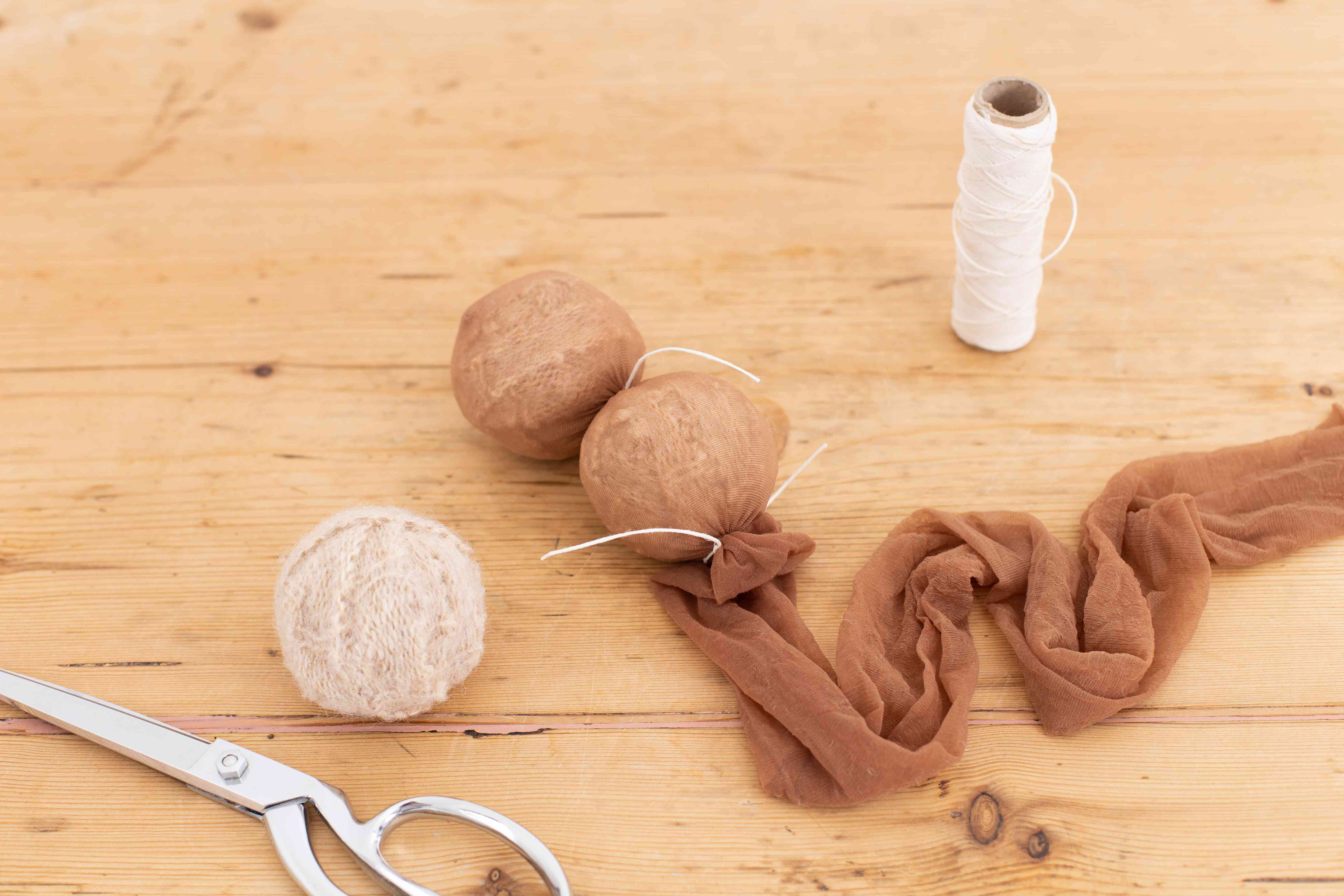 Leg of pantyhose wrapping dryer balls and tied with cotton string