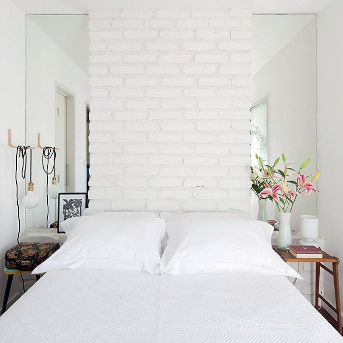 bedroom with a bed in front of a brick wall